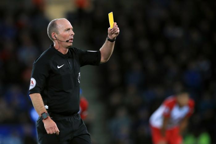 Mike Dean shows a yellow card during a Premier League fixture