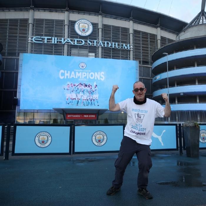 A Manchester City fan celebrates their 2020/21 Premier League title
